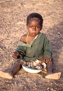 An impoverished child from West Africa finishing a meal.  Photo by Jim Whitmer