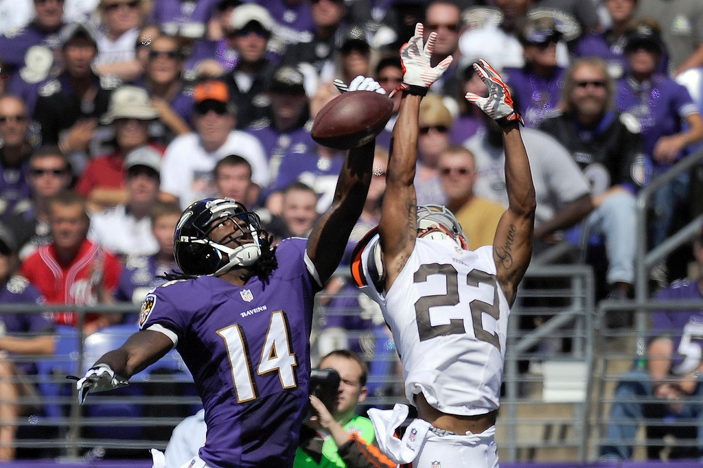 . Baltimore Ravens wide receiver Marlon Brown (14) cannot hang on to a pass under pressure from Cleveland Browns cornerback Buster Skrine (22) during the first half of a NFL football game in Baltimore, Md., Sunday, Sept. 15, 2013. (AP Photo/Nick Wass)