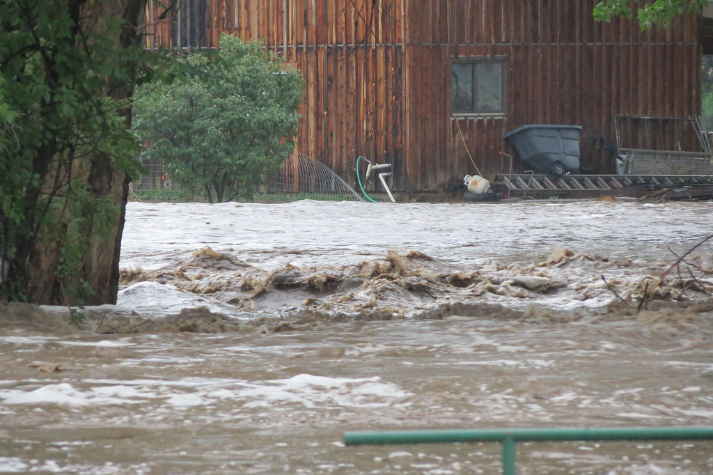 . The Big Thompson River consumes the entire yard and is moments from reaching this house across the river from Mariana Butte in Loveland, Colorado. Photo by Mike Garcia