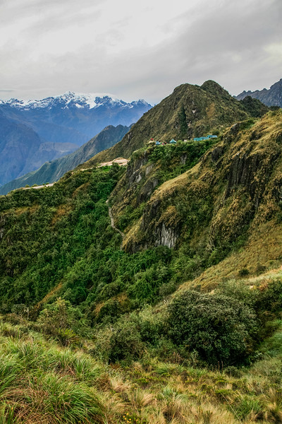 Camping along the Inca trail, there are a number of tents with high peaks in the background