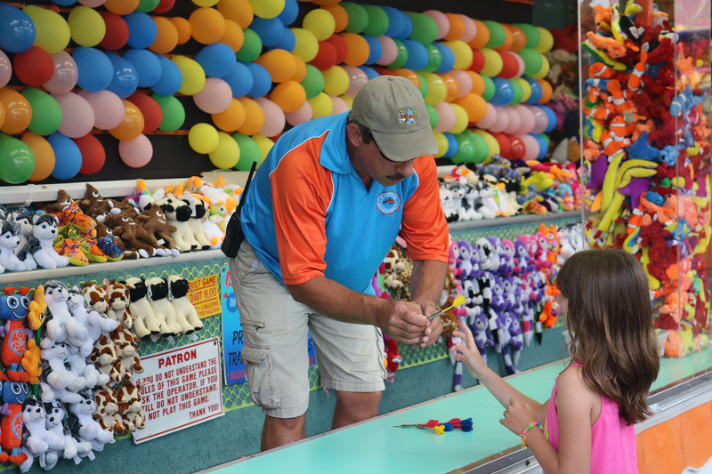LUCAS FORTNEY / GAZETTE Chuck Harrison explains the rules of his station to a young girl and hands her a dart for a practice throw at an arcade event Friday at the Brunswick Summer Celebration. Harrison has operated his traveling station for 28 years in a row and said he was excited to see that folks came out despite the weather.