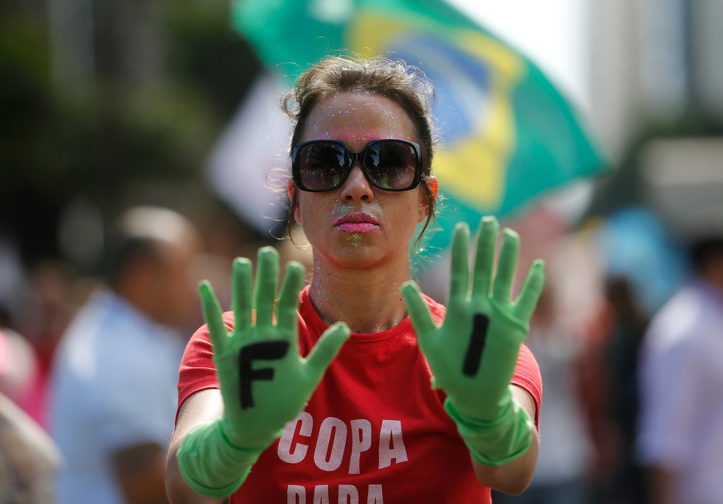 . An anti-World Cup demonstrator holds up her hands, wearing rubber gloves with the first two letters of the acronym, FIFA, during a protest demanding better public services and protesting the money spent on the World Cup soccer tournament, in downtown Rio de Janeiro, Brazil, Thursday, June 12, 2014, just hours before the opening match was to be played in Sao Paulo. (AP Photo/Silvia Izquierdo)