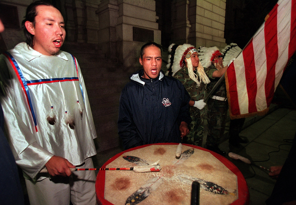 . [sandcreek 1]  Caption: Eugene Ridgely (left), lead singer for the River Bottom  Junior singing group and a member of the Nothern Arapahoe Tribe  from Arapahoe, Wyoming, and Larry Sioux (middle in blue coat), a  member of the Cheyenne Sioux Tribe, sing an honor song before the  beginning of the candlelight vigil Sunday night, November 28, 1999 on the west steps  of the State Capital remembering those killed during the Sand  Creek Massacre in 1864. This is the 135th anniversary of the  massacre and was remembered by a170 mile spiritual healing run  beginning at the site this past Friday and ending Monday morning. (LEW SHERMAN/THE DENVER POST)