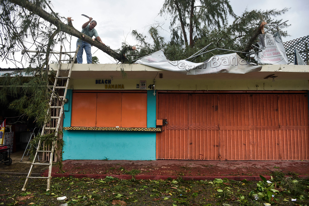 . An employee works to remove a felled tree from a rooftop in the aftermath of Hurricane Irma, in Fajardo, Puerto Rico, Thursday, Sept. 7, 2017. Irma cut a path of devastation across the northern Caribbean, leaving at least 10 dead and thousands homeless after destroying buildings and uprooting trees. More than 1 million people in Puerto Rico are without power. (AP Photo/Carlos Giusti)