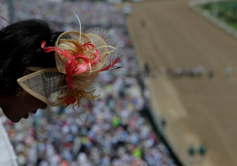 . A woman looks out over a balcony before the 140th running of the Kentucky Derby horse race at Churchill Downs Saturday, May 3, 2014, in Louisville, Ky. (AP Photo/Charlie Riedel)