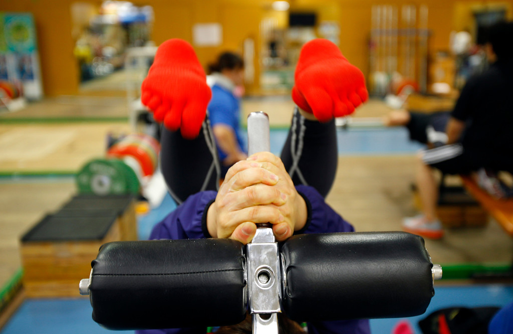 . In this Friday, Aug. 30, 2013 photo, Japanese weightlifter Hiromi Miyake, silver medalist in the London Olympic women\'s 48kg event, warms up before her training at one of Tokyo\'s leading training centers. The Olympics are in Miyake\'s blood, a heritage that stretches back to the 1960s, when her uncle won a gold medal at the 1964 Tokyo Games and her father won bronze in Mexico City in 1968. With the Olympics coming to Tokyo in 2020, she hopes that will inspire the next generation of Japanese athletes. (AP Photo/Junji Kurokawa)