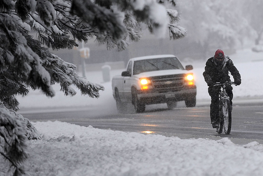 . A bicyclist and a motorist share a snowy roadway in Fort Collins, Colo. during the snowstorm that hit northern Colorado Wednesday morning May 1, 2013. (AP Photo/The Coloradoan, Rich Abrahamson)