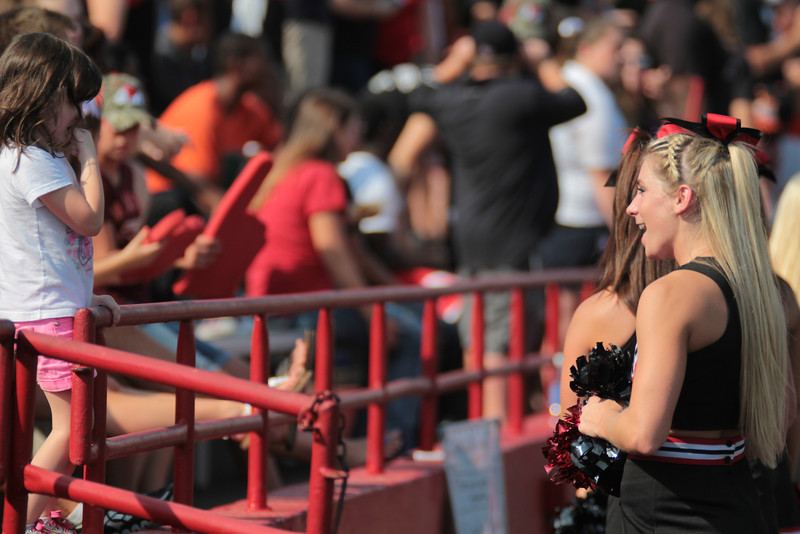 A cheerleader talks to a young fan.