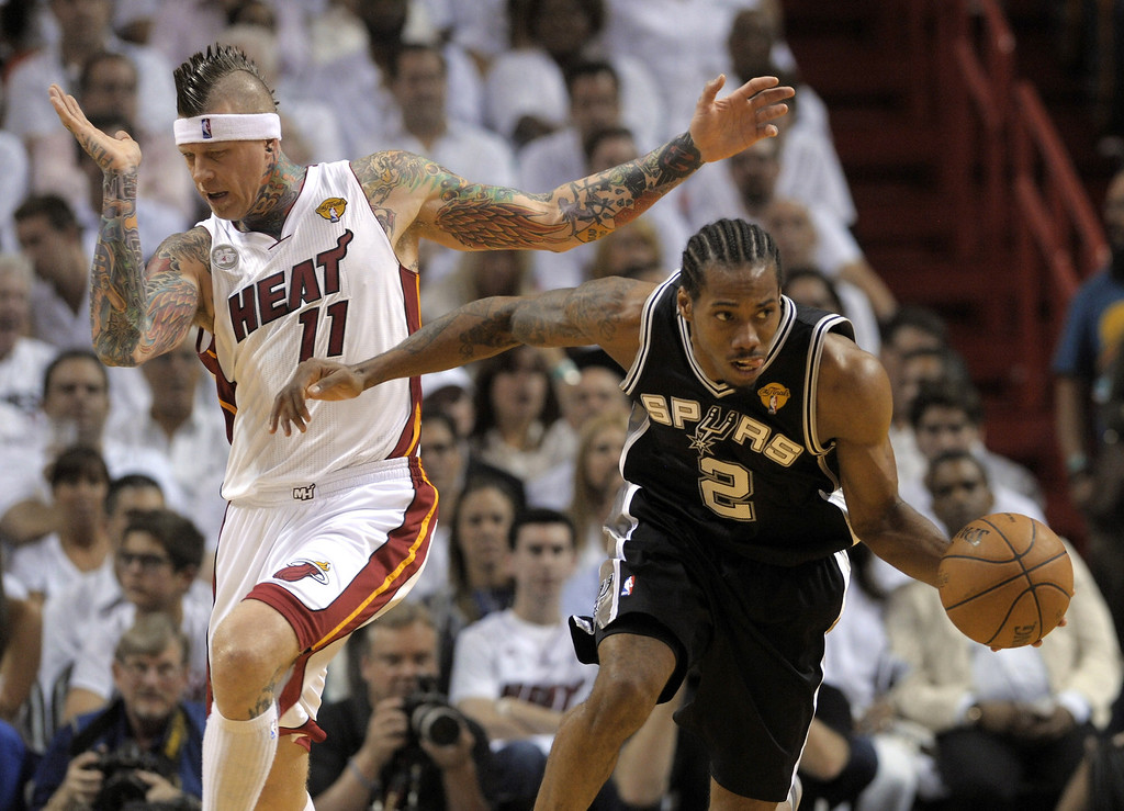 . Kawhi Leonard (R) of the San Antonio Spurs breaks away from Chris Andersen (L) of the Miami Heat in the first half during Game 1 of the NBA Finals on June 6, 2013 at American Airlines Arena in Miami, Florida.   BRENDAN SMIALOWSKI/AFP/Getty Images
