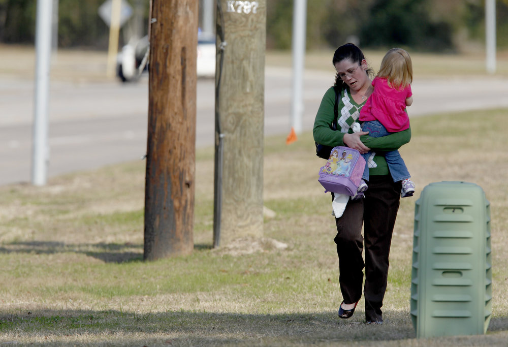 Description of . Tierna Tate carries her 19th month old daughter Olivia Tate after she picked her up from the Lone Star College Daycare on January 22, 2013 in The Woodlands, Texas. According to reports, three people were injured during a shooting on the courtyard between the Library and cafeteria.  (Photo by Thomas B. Shea/Getty Images)