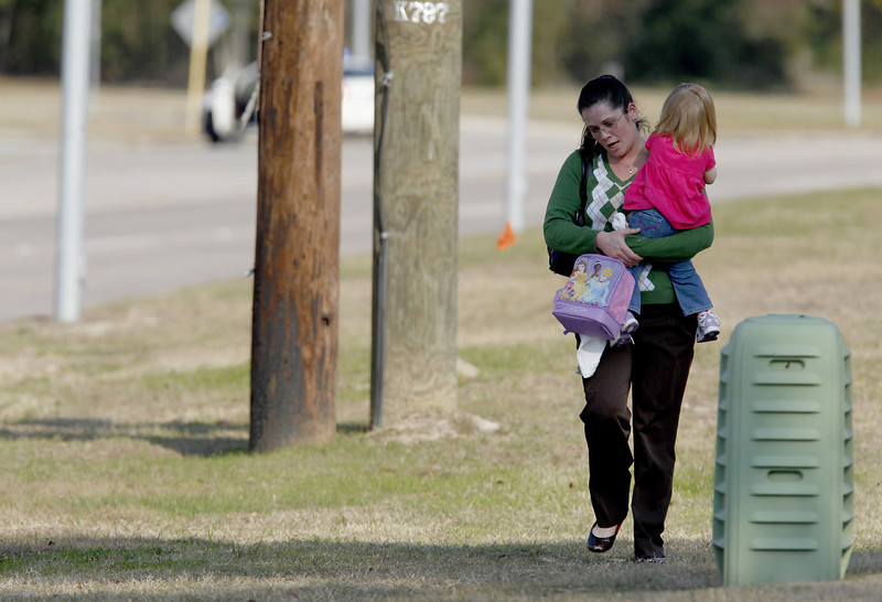 . Tierna Tate carries her 19th month old daughter Olivia Tate after she picked her up from the Lone Star College Daycare on January 22, 2013 in The Woodlands, Texas. According to reports, three people were injured during a shooting on the courtyard between the Library and cafeteria.  (Photo by Thomas B. Shea/Getty Images)