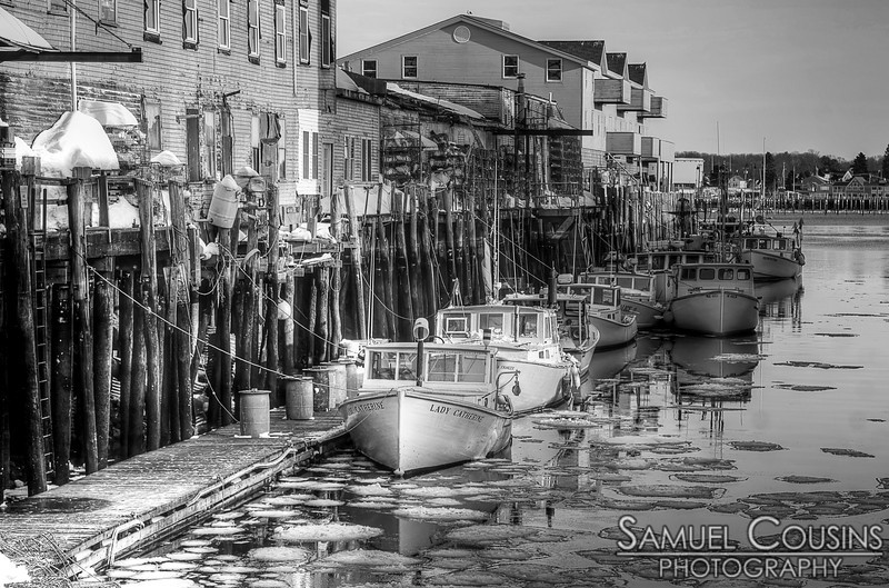 Boats docked on a wharf. in black and white.