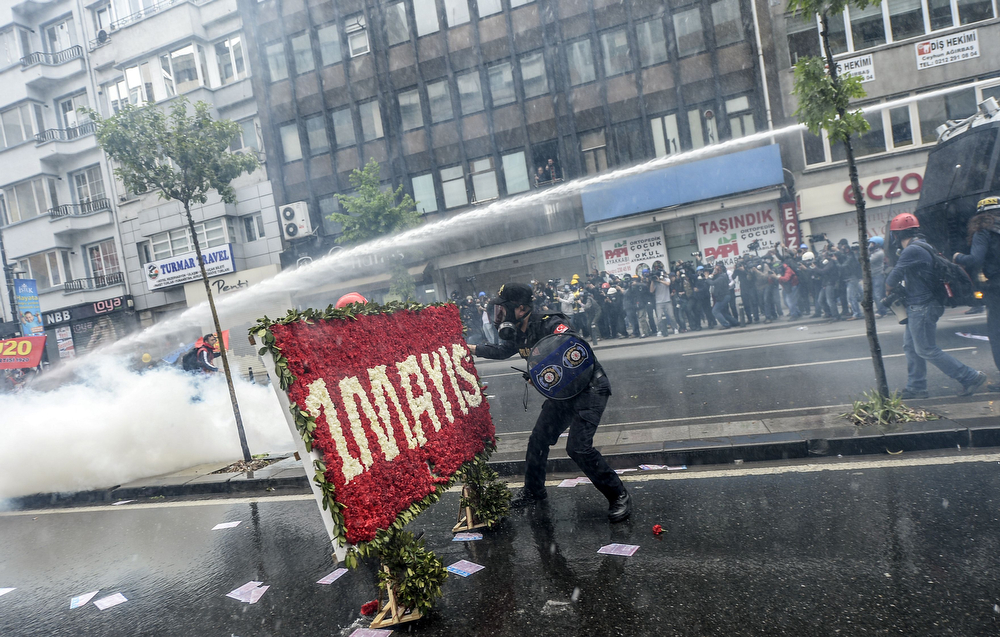 ". A Turkish policeman tries to remove a banner made of flowers reading ""First of May\"" as police try to disperse a May Day rally near Taksim Square in Istanbul on May 1, 2014. Turkish police used water canon and tear gas to disperse thousands of protesters who tried to defy a Labour Day ban on demonstrations on Istanbul\'s Taksim Square, the scene of protests that have dogged the government for months. (BULENT KILIC/AFP/Getty Images)"