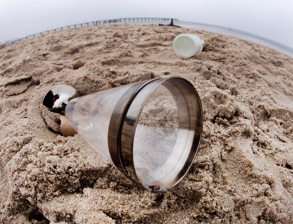 . A champagne glass and a bottle lie at the beach of the Baltic Sea in Timmendorfer Strand, northern Germany, Sunday, Jan. 1, 2017 after a New Year\'s Eve party with thousands attending. (AP Photo/Michael Probst)