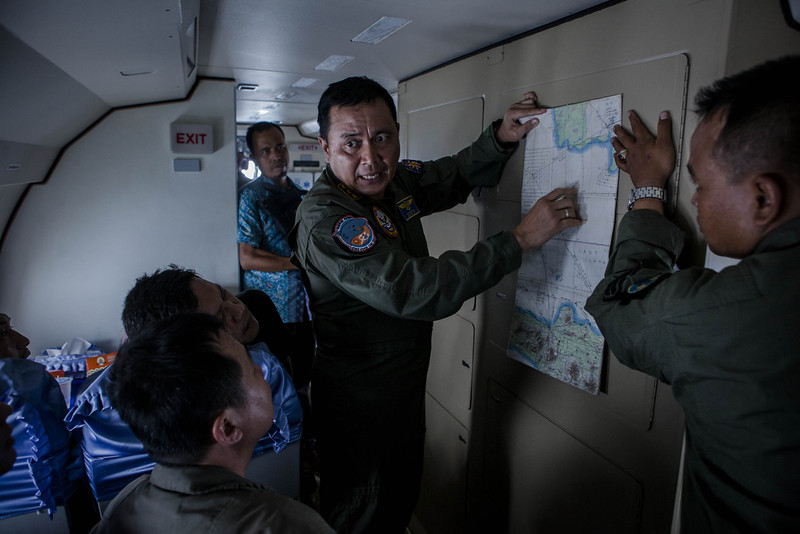 . A member of the Indonesian military reads a map during a search and rescue (SAR) mission over the waters of the Java Sea near Pangkalan Bun, Kalimantan on December 30, 2014 in Surabaya, Indonesia. Debris and dead bodies have reportedly been sighted in the Java Sea during search operations for the missing AirAsia flight QZ 8501. AirAsia flight QZ8501 from Surabaya to Singapore, with 162 people on board, lost contact with air traffic control at 07:24 a.m. local time on December 28. (Photo by Ulet Ifansasti/Getty Images)