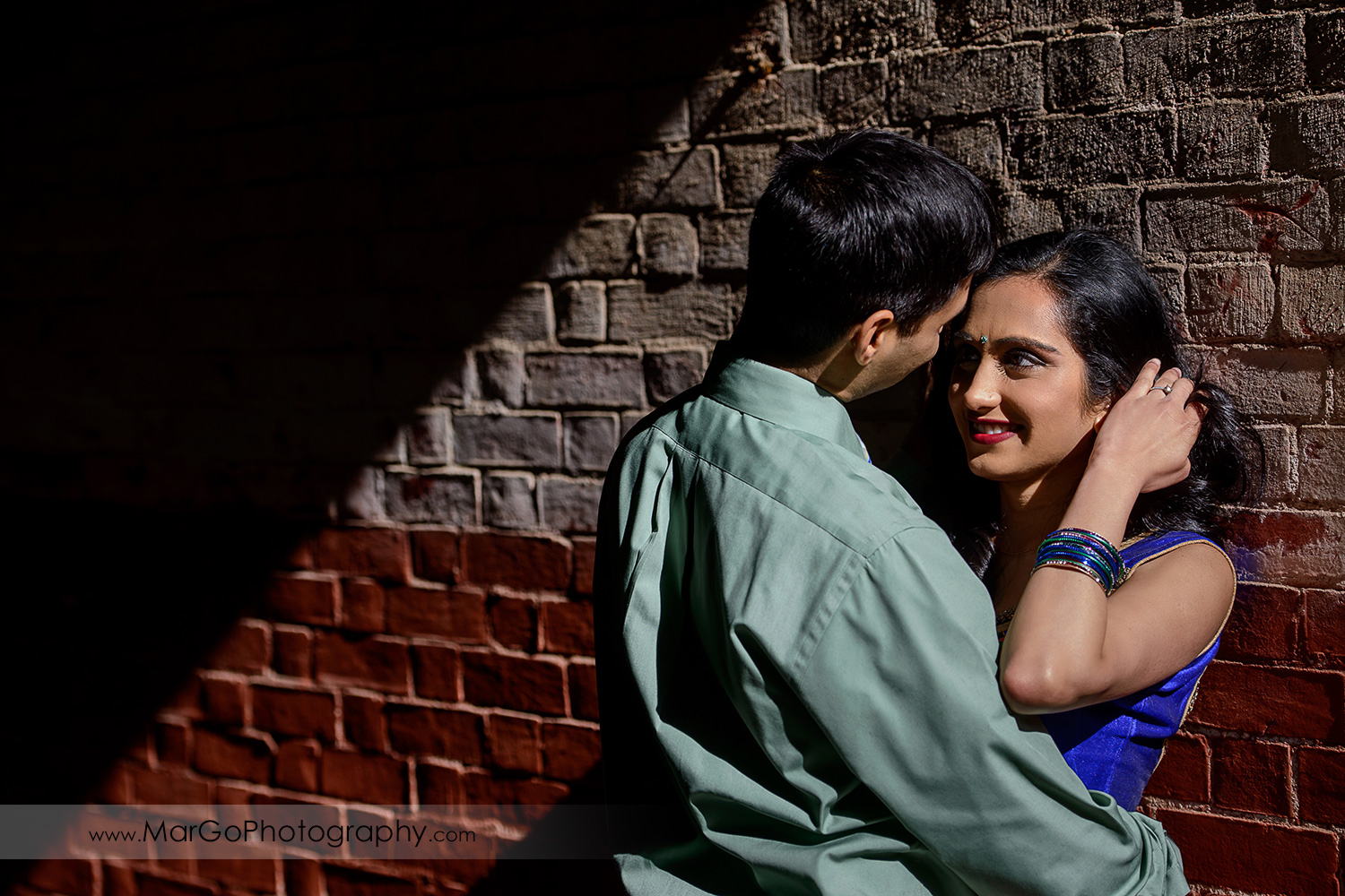 portrait of Indian couple looking at each other on the brick wall during engagement session at San Francisco Fort Point