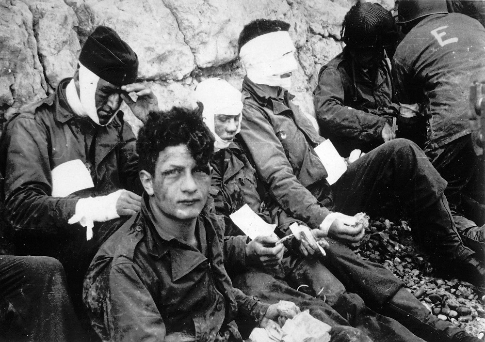 Description of . Men of the American assault troops of the 16th Infantry Regiment, injured while storming a coastal area code-named Omaha Beach during the Allied invasion of the Normandy, wait by the chalk cliffs at Collville-sur-Mer for evacuation to a field hospital for further treatment, in this June 6, 1944 file photo. (AP Photo, File)