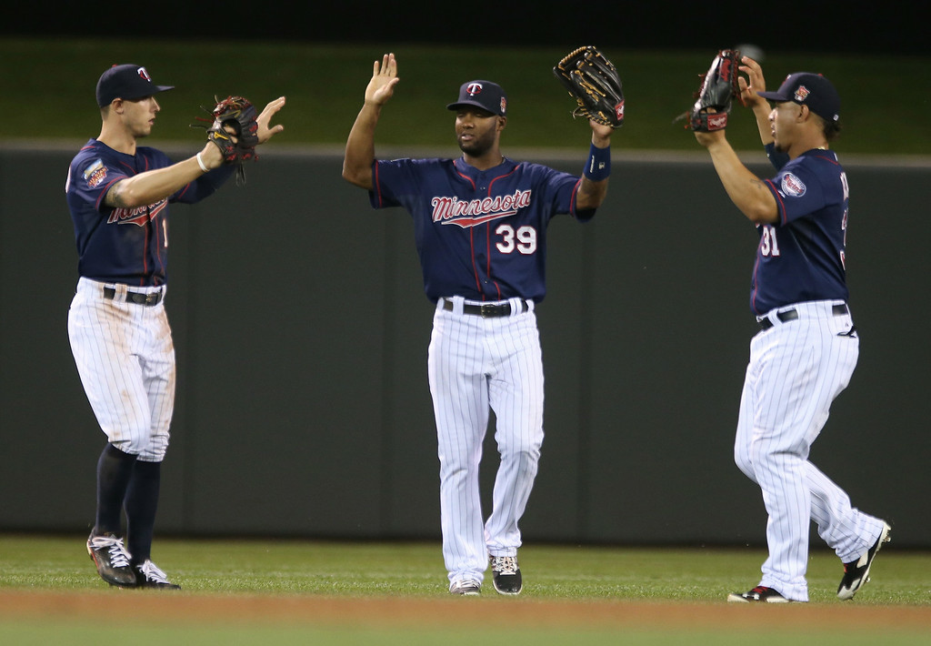 . Minnesota Twins outfielders, from left, Jordan Schafer, Danny Santana and Oswaldo Arcia celebrate after the Twins defeated the Detroit Tigers 20-6 in a baseball game, Friday, Aug. 22, 2014, in Minneapolis. Santana drove in four runs in the game. (AP Photo/Jim Mone)