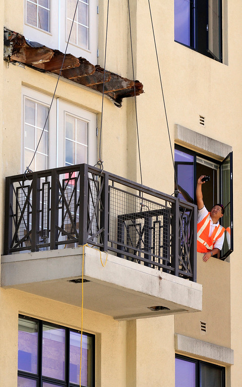 . Inspectors who did not want to be identified use a window to get different photos of the rotted wood beams and the lower balcony outside the residential apartment building on Kittredge Street in Berkeley, Calif. on Wednesday, June 17, 2015.  Six people died and seven others were seriously injured when the balcony collapsed early Tuesday morning during a birthday party.(Laura A. Oda/Bay Area News Group)