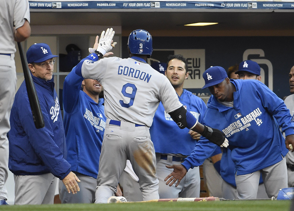 . Dee Gordon #9 of the Los Angeles Dodgers is congratulated after scoring during the fifth inning of a baseball game against the San Diego Padres on Opening Night at Petco Park on March 30, 2014 in San Diego, California.  (Photo by Denis Poroy/Getty Images)