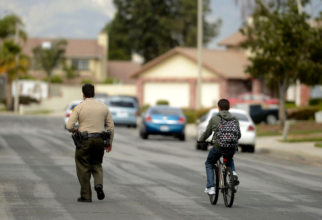 . A San Bernardino County Sheriff\'s Deputy escorts a boy to his home as police search for pursuit suspects along the 100 block of East Meadow Lane in Rialto April 16, 2013.   GABRIEL LUIS ACOSTA/STAFF PHOTOGRAPHER.