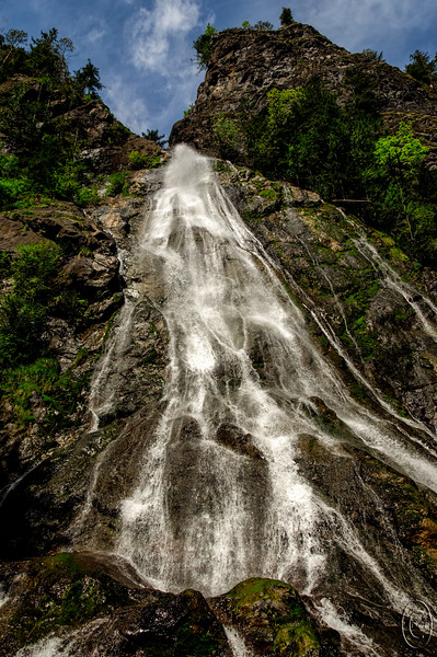 """27 Apr 16.   Last year I shared a couple of shots from a falls on the west side of Hood Canal called Rocky Brook Falls. This is an extremely easy falls to visit as it is just a one block walk from where you park on a well maintained path. The only challenge is that it is not marked in any manner. You need to know where it is to go visit it. We found out about it by accident, but it was definitely one of those good accidents. There was not a huge amount of water falling today, but there was enough that it was shooting outward where the water began its downward flow and made for an interesting """"look"""" at the top of the falls. Today's visit was our first where we actually had an interesting sky, blue with white clouds as opposed to the more common flat gray we've experienced on all are prior visits. Water level and winds low and nice sunshine allowed for a positioning close to the base of the falls that didn't result in the camera getting a bath, so the shot for today is quite a bit different from those I've shared previously.  The base image was give a little chromatic aberration adjustment and that was it. Nikon D300s; 18 - 200; Aperture Priority; ISO 200; 1/1000 sec @ f / 8."""