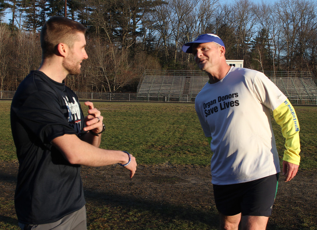 . Donald Davis, 54, of Reading, right, will run the Boston Marathon route Sunday a week early to raise money for DonateLife and promote organ and tissue donation. His nephew Bryon Patten, 34, of Woburn, left, will run with him forwards to keep him on course. Both are originally from Billerica. They stretch after a workout at the Marshall Middle School track. (SUN/Julia Malakie)