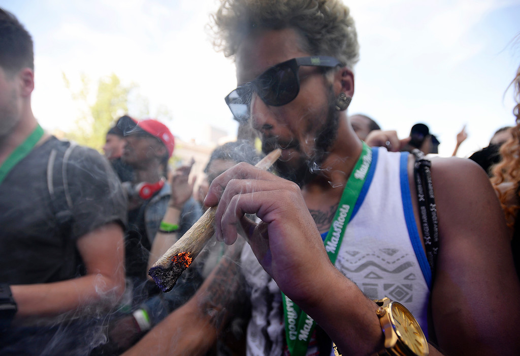 . A man smokes a giant blunt during the Denver 420 Rally held Saturday at Civic Center Park. (Photo by Kira Horvath/ The Denver Post)