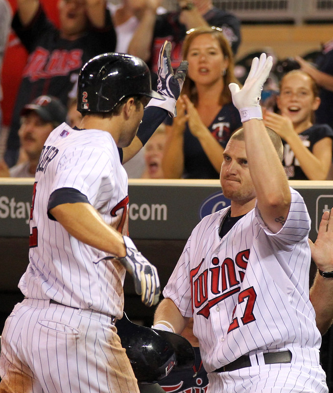 . Minnesota Twins Brian Dozier is congratulated by teammate Chris Parmelee (17) after Dozier scored in the seventh inning of their baseball game won by the Twins 6-3 in Minneapolis Monday, Sept. 9, 2013.(AP Photo/Andy Clayton-King)