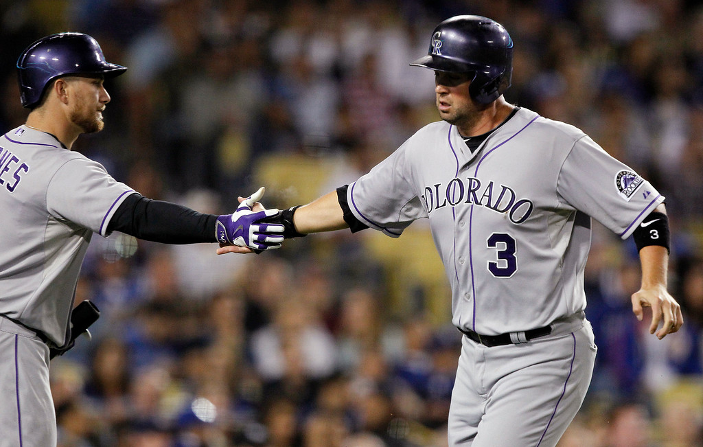 . Colorado Rockies Michael Cuddyer (3) gets congratulations from Brandon Barnes after scoring on a double by Kyle Parker in the fourth inning of a baseball game against the Los Angeles Dodgers Saturday, Sept. 27, 2014 in Los Angeles. (AP Photo/Alex Gallardo)