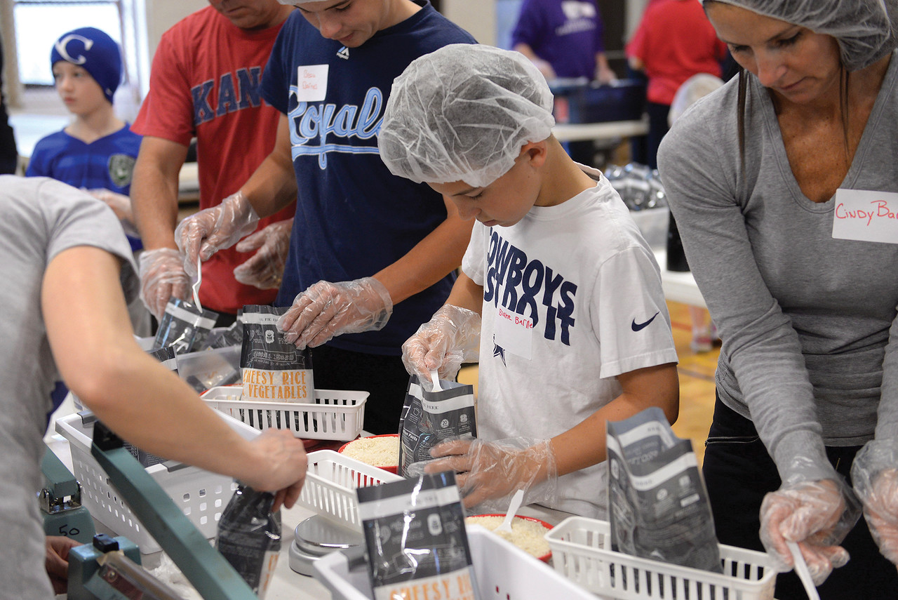 From left (with Royals shirt), Beau, Blake and Cindy Barnes take part in a packing party in the gymnasium of Curé of Ars School in Leawood. Workers poured cups of rice, soy, vegetables, vitamins and cheese into a bag that would be distributed later by the organization Something to Eat. Leaven photo by Joe McSorley