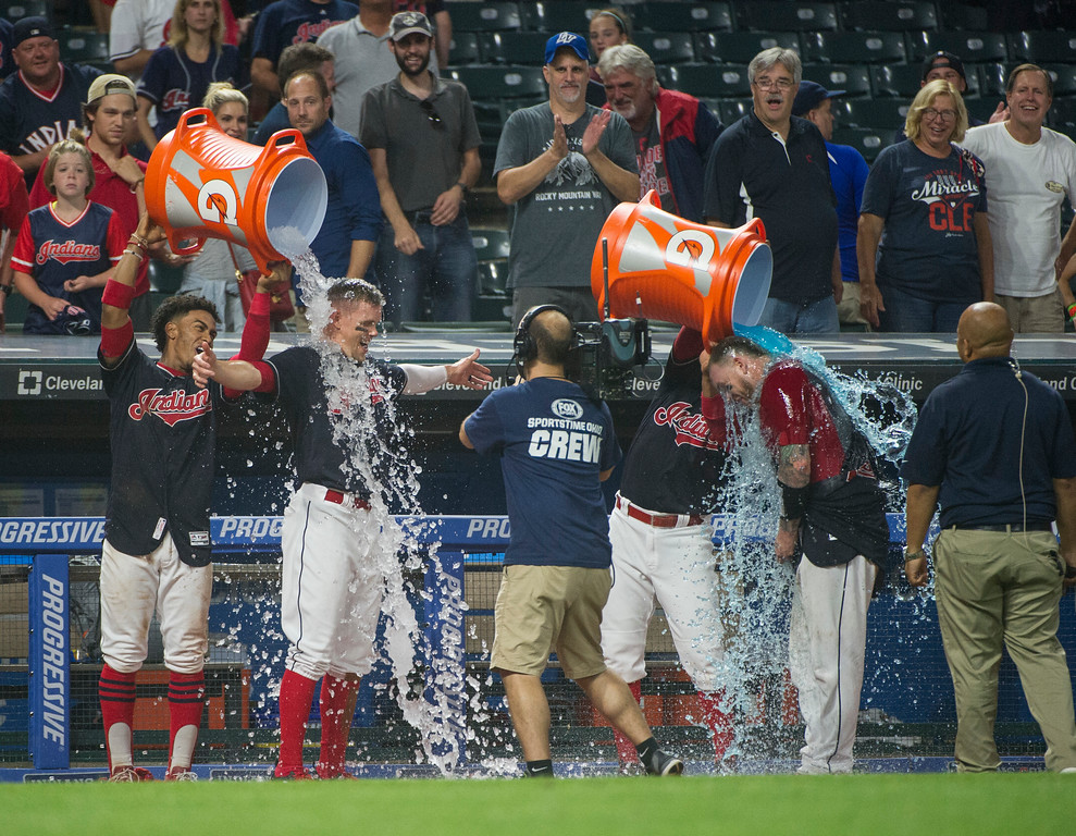 . Cleveland Indians\' Brandon Guyer, arms outstretched, is doused by teammate Francisco Lindor as Roberto Perez get a bucket as well after beating the Boston Red Sox in the ninth inning of a baseball game in Cleveland, Monday Aug. 21, 2017. Perez laid down a bunt that turned into a throwing error by the Red Sox\' Brock Holt allowing Guyefr to score from second base. The Indians won 5-4. (AP Photo/Phil Long)