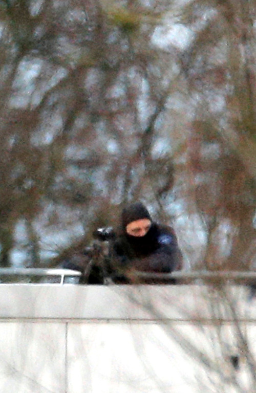 . A hooded police officer stands on a roof in Dammartin-en-Goele, northeast of Paris, where the two brothers suspected in a deadly terror attack were cornered, Friday, Jan.9, 2015. Two sets of attackers seized hostages and locked down hundreds of French security forces around the capital on Friday, sending the city into fear and turmoil for a third day in a series of linked attacks that began with the deadly newspaper terror attack that left 12 people dead. (AP Photo/Christophe Ena)