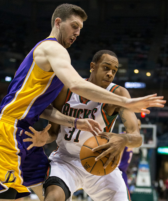 . Milwaukee Bucks\' John Henson spins away from Los Angeles Lakers\' Ryan Kelly during the second half of an NBA basketball game Thursday, March 27, 2014, in Milwaukee. (AP Photo/Tom Lynn)