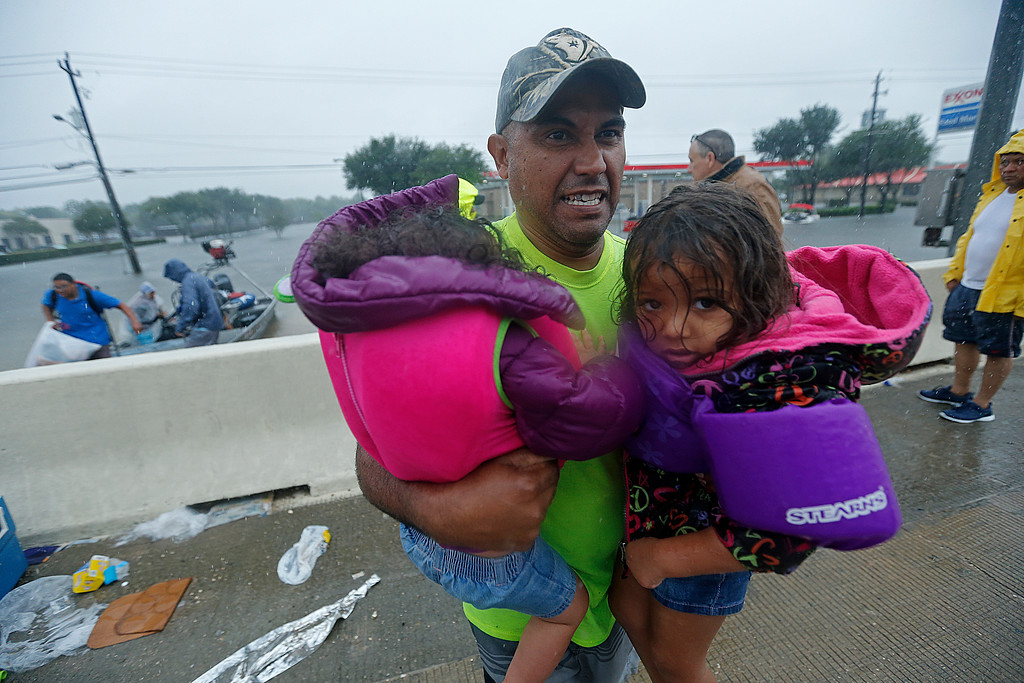 . A man carries children after being rescued by members of the Louisiana Department of Wildlife and Fisheries and the the Houston Fire Department after residents were stranded by floodwaters due to Tropical Storm Harvey, Monday, Aug. 28, 2017. (AP Photo/Gerald Herbert)