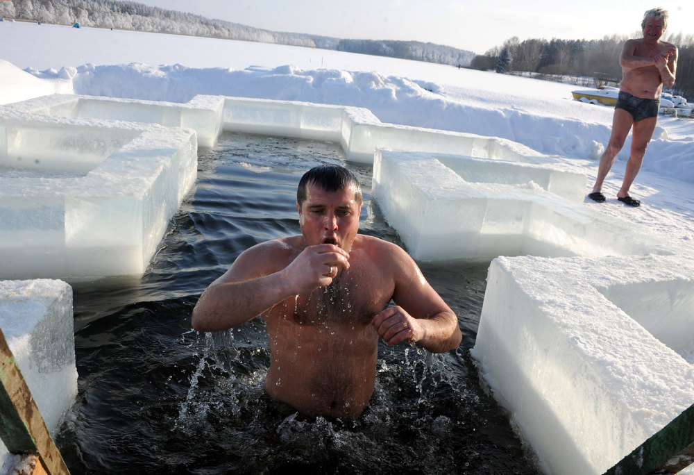 Description of . A Belarus Orthodox believer plunges into icy waters on the eve of the Epiphany holiday in Pilnitsa some 30 km outside Minsk, on January 18, 2013. Thousands of believers jumpe into holes cut in ice, braving freezing temperatures, on January 18 and early on January 19 to mark Epiphany, when they take part in a baptism ceremony. VIKTOR DRACHEV/AFP/Getty Images