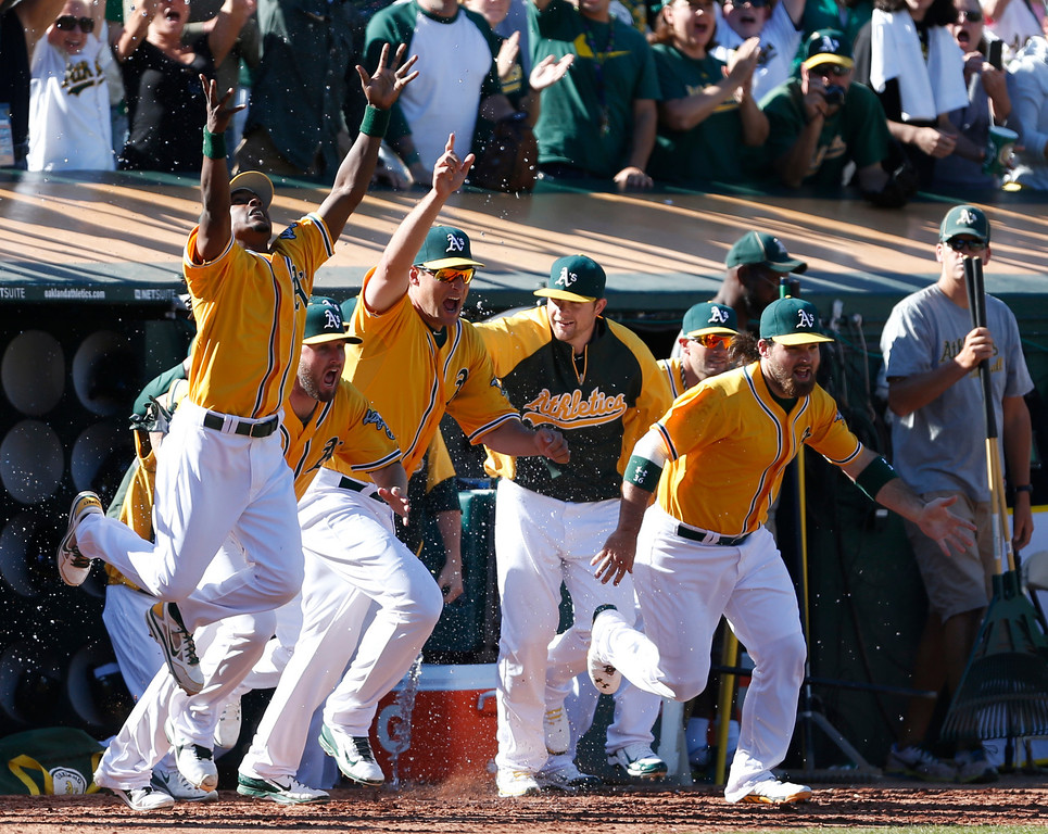 . Oakland Athletics\' Jemile Weeks, left,  Nate Freiman, center, and Derek Norris, right, celebrate as they run out of the dugout after defeating the Minnesota Twins 11-7 in a baseball game to become American League West champions, Sunday, Sept. 22, 2013, in Oakland, Calif. (AP Photo/Beck Diefenbach)