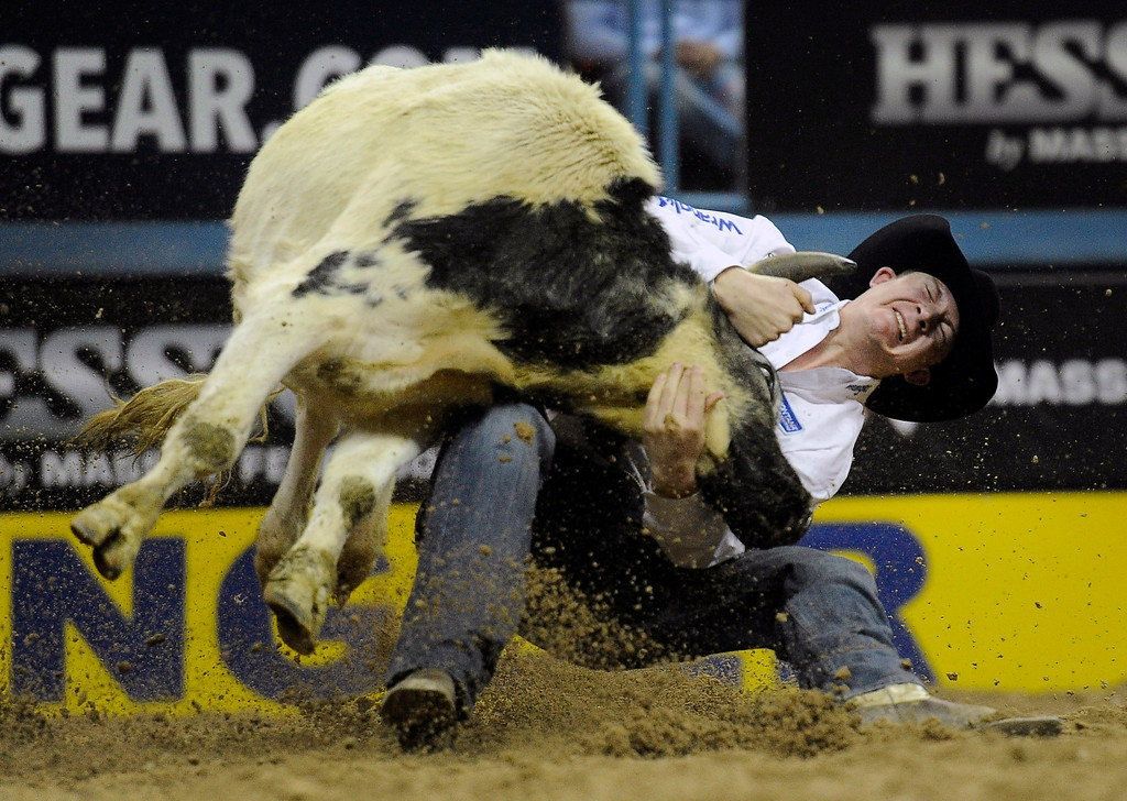 . Ty Erickson of Helena, Mont. competes in steer wrestling during the third go-round of the Wrangler National Finals Rodeo on Saturday, Dec. 6, 2014, in Las Vegas. (AP Photo/Las Vegas Review Journal, David Becker)