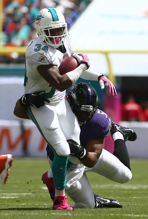 . Baltimore Ravens inside linebacker Daryl Smith (51) tackles Miami Dolphins running back Marcus Thigpen (34) during the first half of an NFL football game, Sunday, Oct. 6, 2013, in Miami Gardens, Fla. (AP Photo/J Pat Carter)
