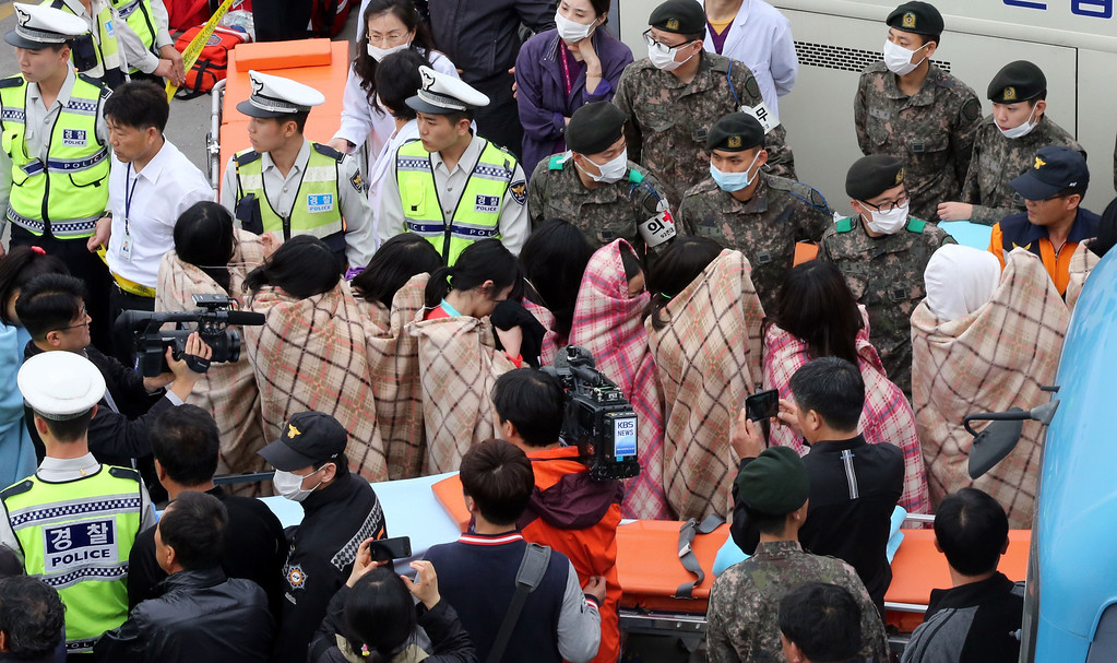. This photo taken on April 16, 2014 shows rescued passengers, wrapped in blankets, being brought onto land in Jindo after a South Korean ferry carrying 477 passengers and crew capsized on its way to Jeju island from Incheon. South Korea said on April 16 that two people were killed and 368 rescued from a ferry that capsized at sea with 477 people on board -- mostly high school students -- as divers searched for scores still missing.    AFP PHOTO/YONHAPYONHAP/AFP/Getty Images