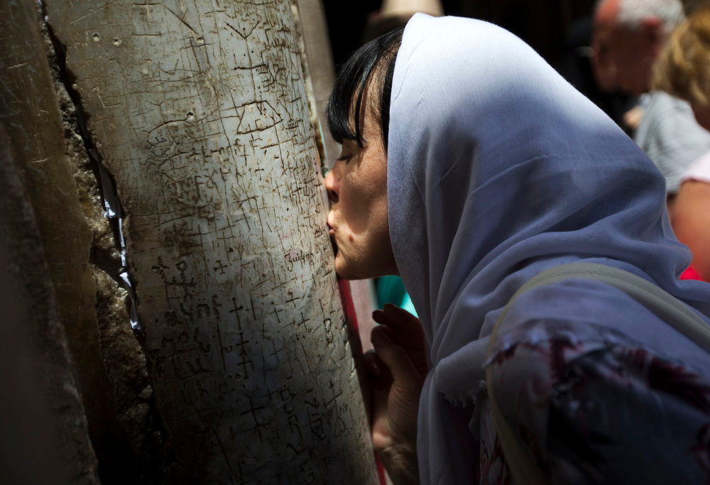 . A Christian worshipper kisses a pillar at the entrance to the Church of the Holy Sepulchre in Jerusalem\'s Old City, before the Orthodox Easter service, May 5, 2013. REUTERS/Ronen Zvulun