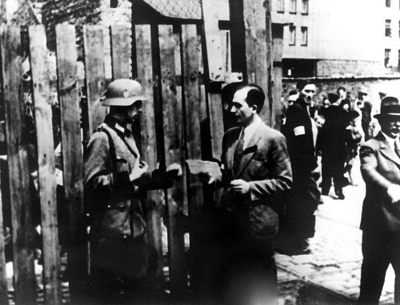 . A street scene with a German nazi soldier checking someone\'s papers in the Warsaw Jewish ghetto during World War II.   (AFP/Getty Images)