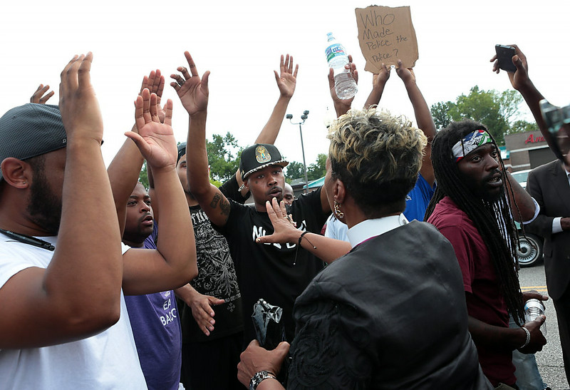 . Protestors blocking Florissant Road get in a brief confrontation with members of the clergy who asked them to leave the street and come pray with them in front of the Ferguson, Mo. police department on Sunday, Aug. 10, 2014, one day after a Ferguson officer shot and killed Michael Brown. (AP Photo/St. Louis Post-Dispatch, Robert Cohen)