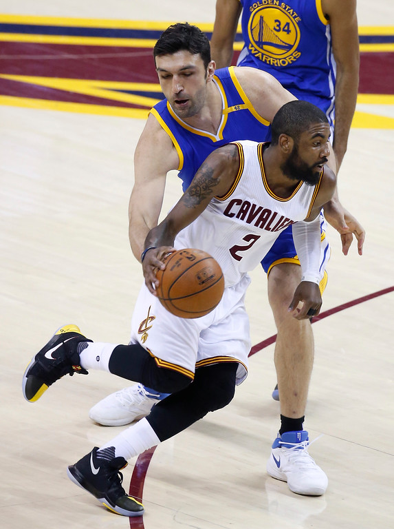 . Cleveland Cavaliers guard Kyrie Irving (2) drives on Golden State Warriors center Zaza Pachulia, rear, during the first half of Game 3 of basketball\'s NBA Finals in Cleveland, Wednesday, June 7, 2017. (AP Photo/Ron Schwane)