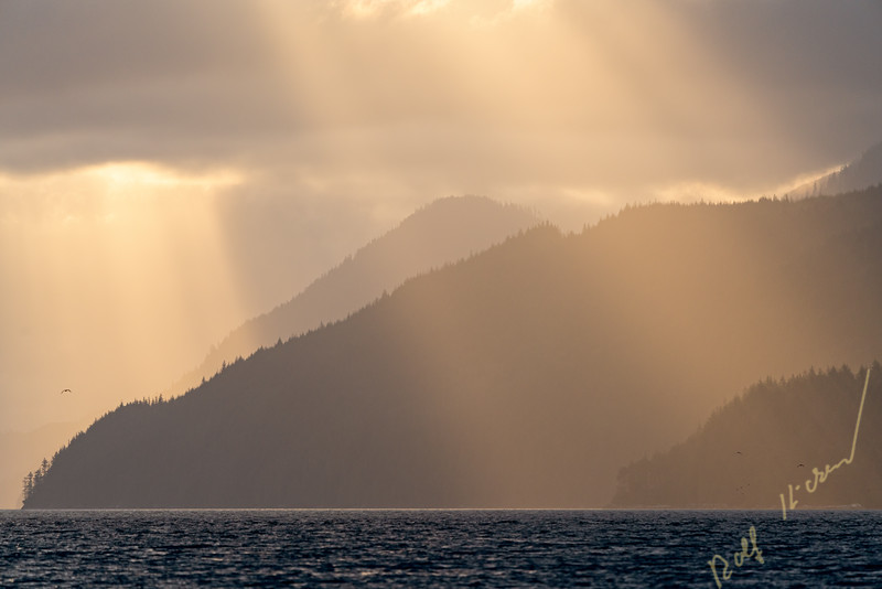 Early colorful morning in beautiful Knight Inlet with sun rays between the clouds, First Nations Territory, British Columbia, Canada