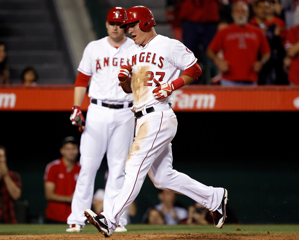 . Los Angeles Angels\' Mike Trout (27) scores on a single by Angels designated hitter Albert Pujols (not pictured) against the Seattle Mariners in the sixth inning during a baseball game Tuesday, May 21, 2013 in Anaheim. On deck batter Los Angeles Angels first baseman Mark Trumbo, left, looks on as Trout scores.   (AP Photo/Alex Gallardo)