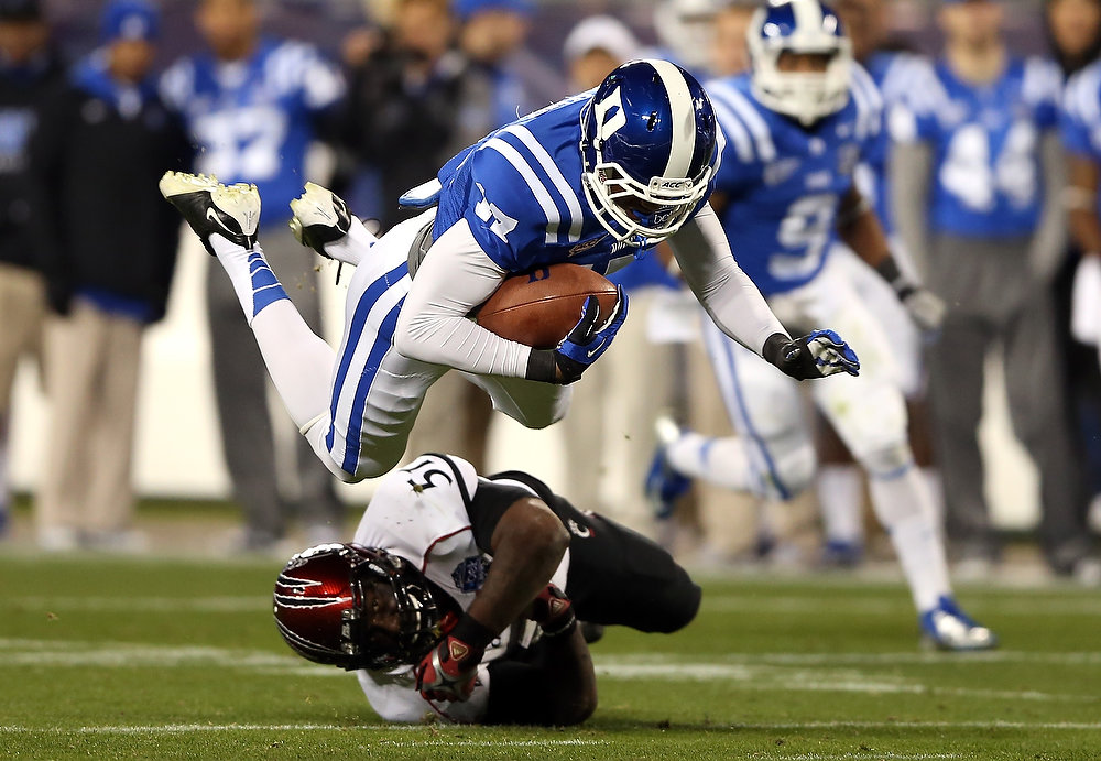 Description of . Greg Blair #51 of the Cincinnati Bearcats tries to stop Issac Blakeney #17 of the Duke Blue Devils as he jumps into the air during their game at Bank of America Stadium on December 27, 2012 in Charlotte, North Carolina.  (Photo by Streeter Lecka/Getty Images)
