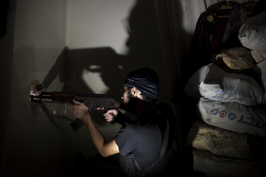 . Opposition fighter Abu Yassin, 21, takes position inside a building in Salaheddin square, in Syria\'s northern city of Aleppo, on September 30, 2013. College student Abu Yassin never imagined picking up a gun and fighting the Syrian regime, but all that changed when he saw a little boy bleeding to death in his father\'s arms.  JM LOPEZ/AFP/Getty Images