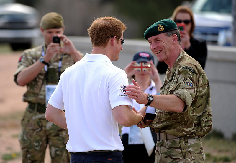 . Major General Buster Howes, OBE, Defense Attache & Head of British Defence, right,  and Prince Harry shake hands and have a laugh after the awards ceremony.  The fourth annual Warrior Games cycling event took started and finished at Falcon Stadium on the grounds of the Air Force Academy in Colorado Springs, CO on May 12, 2013.  HRH Prince Harry was on hand to start the race as well as to hand out medals at the finish line.   A total of 260 wounded, ill and injured service members and veterans came to compete in the week long games.  Members of the Army, Marine Corps, Navy/Coast Guard/Air Force. Special Operations and the British Armed Forces all took part in the competition.  Other events included in the Warrior Games are shooting, sitting volleyball, track & field and wheelchair basketball.  (Photo by Helen H. Richardson/The Denver Post)