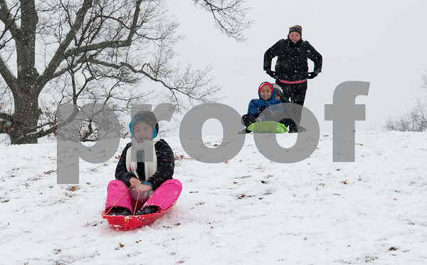 01/17/18 Wesley Bunnell   Staff Christiana Calkins heads down a hill in Walnut Hill Park on Wednesday after snowfall through the day left a new blanket of snow while friends Jayden and Alysse Jackson wait with their mom for their turn.